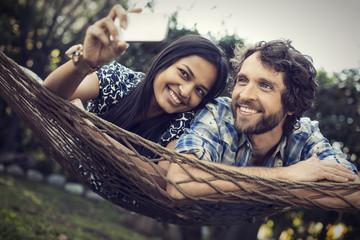 Couple lying in large hammock in garden, taking selfie