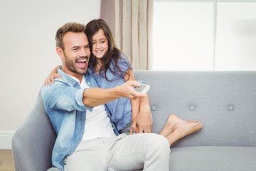 Smiling daughter and father watching television