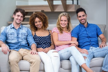 Young friends smiling while sitting on sofa
