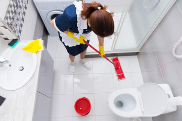 Housekeeper in a hotel mopping a floor