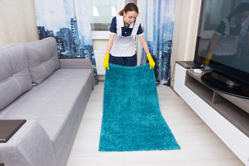 Housekeeper replacing and positioning a rug