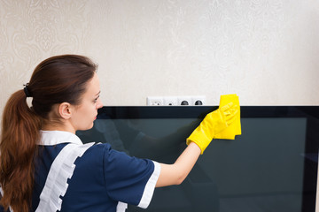Young housekeeper dusting a television set