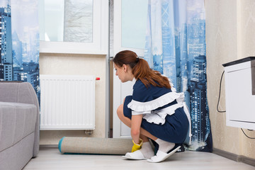 Housekeeper checking the thermostat on a radiator