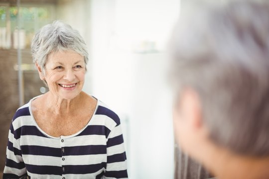 Reflection of happy senior woman on mirror