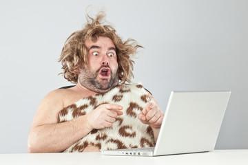 shocked funny prehistoric man using laptop