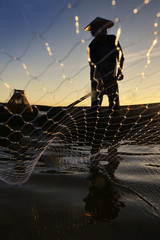 Fishermen while fishing reservoir morning ,Thailand.
