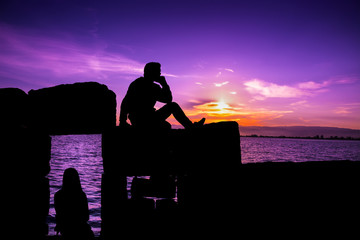 Silhouette of man and girl sitting at sunset
