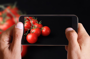 Male hand taking photo of Fresh tomato on black background with cell, mobile phone. Cooking, Healthy eating concept.