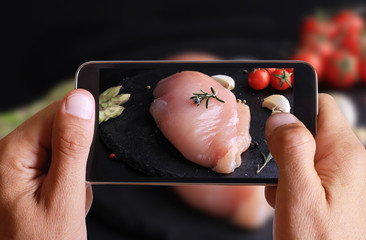 Male hand taking photo of raw chicken breast with spices and cherry tomatoes on wooden background with cell, mobile phone.
