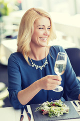 happy woman drinking champagne at restaurant