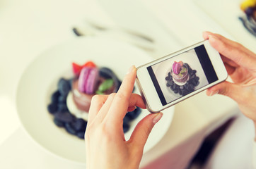 close up of woman picturing food by smartphone