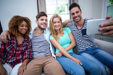 Multi-ethnic friends taking selfie while sitting on sofa