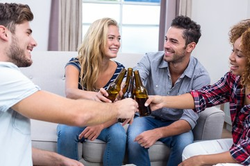 Cheerful friends toasting beer while sitting on sofa