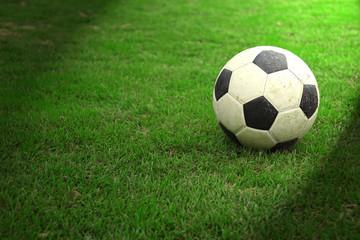 Football on green grass with spot light