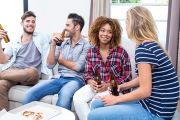 Friends enjoying beer while sitting on sofa at home