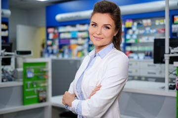 Portrait of beautiful smiling young woman pharmacist standing in