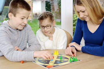 Familie spielt Brettspiel als Gesellschaftsspiel