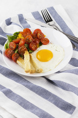 Breakfast: fried eggs with tomatoes and pepper on a white backgr