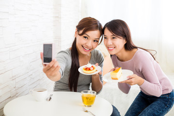 Two beautiful woman having dessert together in coffee shop