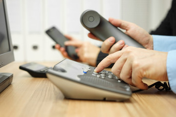 business team is using mobile phone and telephone to contact par