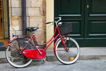 Old red bicycle with wicker basket on the steet of old town, Italy