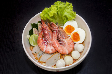 close up. thai noodle seafood (shrimp, eggs, fish ball ) in a cu