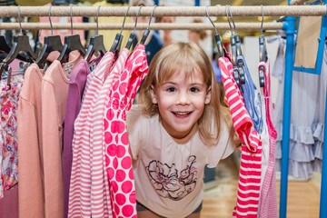 Smiling little girl looks through hangers with clothes. Child has fun in shopping centre.