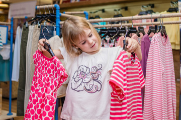 Little girl choose clothes in boutique. Shopping day.