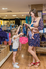 Young mother with two daughters buy baby clothes in shopping centre