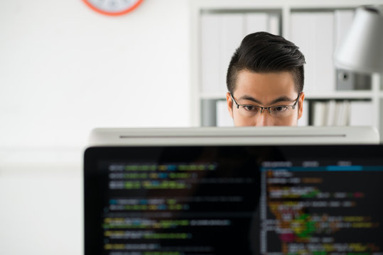 Pensive programmer working on computer in office