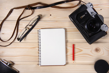 Retro camera with blank notebook on wooden table