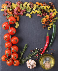 pasta of different colors, tomatoes, garlic, pepper, rosemary in