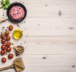 cooking burgers, ground beef with herbs and cherry tomatoes on a branch border ,place for text  on wooden rustic background top view