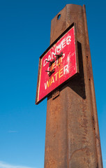 Red danger deep water warning hazard sign on a rusty metal beam.