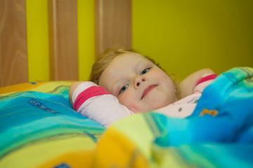 Small girl in sheets on a wooden bed, going to sleep