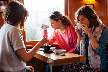 Three teenage girls enjoy their coffee