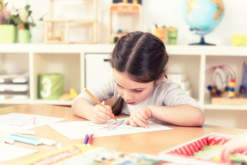 beautiful little girl drawing in her sunny room