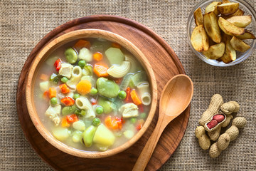 Bolivian traditional Sopa de Mani (peanut soup) made of meat, pasta, vegetables (pea, carrot, potato, broad bean, pepper, corn) with ground peanut, photographed with natural light