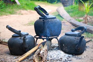 Antique black kettles or coffeepot on an open fire