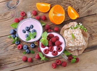 Breakfast. Yogurt with berries blueberries and raspberries, slices and ripe orange.Healthy eating.