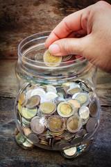 Still life coins in plastic jar.