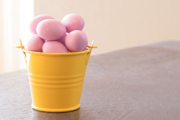 Yellow bucket with violet easter eggs