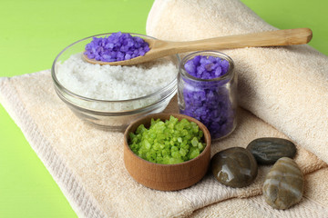 sea salt poured in glass and a wooden bowl with a wooden spoon and fluffy towel with smooth stones on a green background