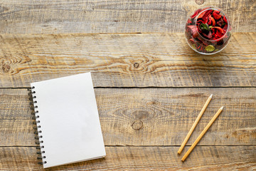 Composition of notebook and pencil at wooden table