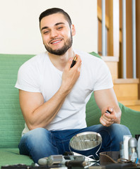 Young guy using perfume at home.