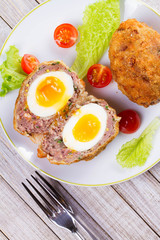 Scotch Eggs Served with Tomato Cherry and Salad on White Plate. View From Above, Top Studio Shot
