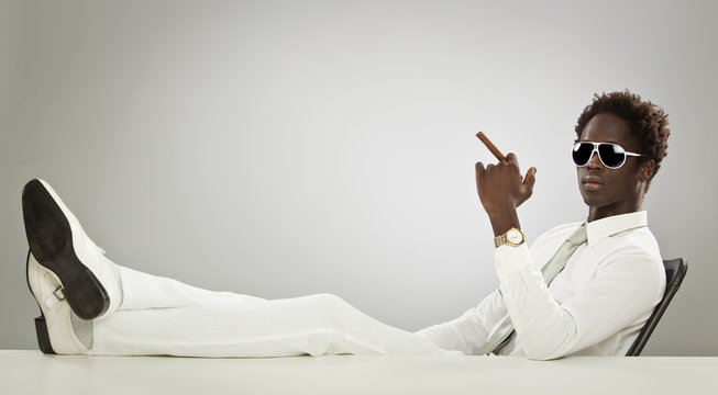 handsome black businessman with white suit smoking cigar at office