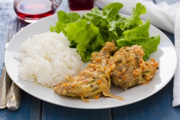 rabbit with boiled rice and salad on white plate