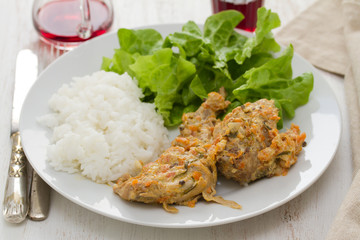 rabbit with sauce,  boiled rice and lettuce on plate and red wine