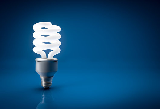 Glowing energy saving bulb over blue background